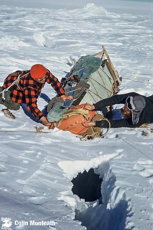 Laden sledge slumped into dangerous crevasse, Mawson Glacier - NZARP's Keith Wise on left and Ray Logie unload the sledge so it can be extracted. Travelling on crevassed glacier with skidoos and dog teams - Nov 1962