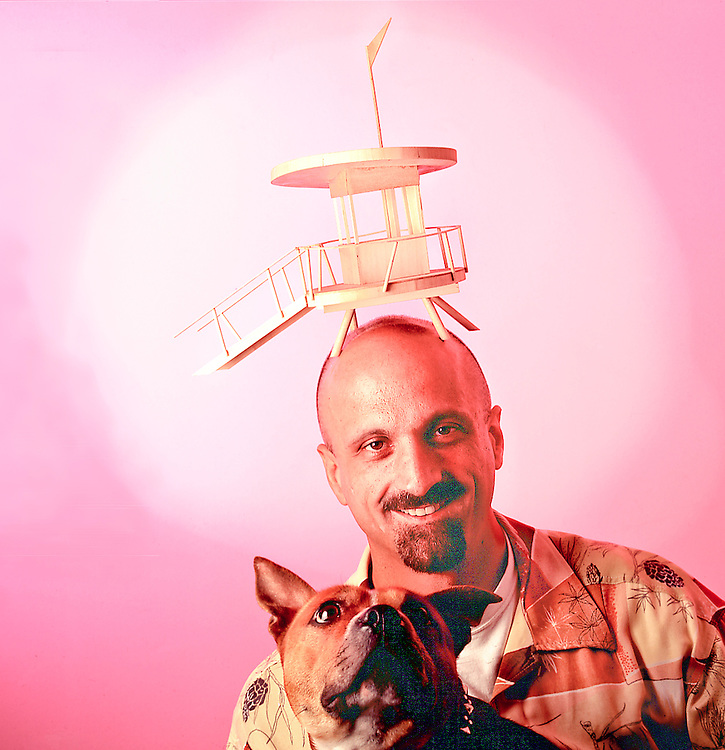 Architect Bill Lane with a model of a landmark Miami Beach lifeguard stand that he designed -- plus Bill's dog, Buster.