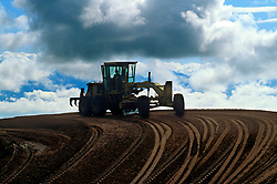 Stock photo of a tractor at the top of a curving dirt road