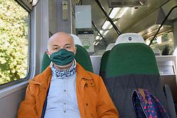 Man wearing face mask on Great Western Railway train, Cornwall UK Oct 2020. MR