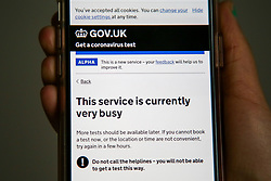 © Licensed to London News Pictures. 21/09/2020. London, UK. A woman holds a phone which displays that the COVID-19 testing booking service is currently very busy. In the past few days, the number of cases of the coronavirus have increased across the UK and the NHS is urging people experiencing a persistent cough, fever or altered sense of taste or smell to seek a coronavirus test. The government is considering rationing the coronavirus tests for the general public as the numbers of positive tests rises. Photo credit: Dinendra Haria/LNP