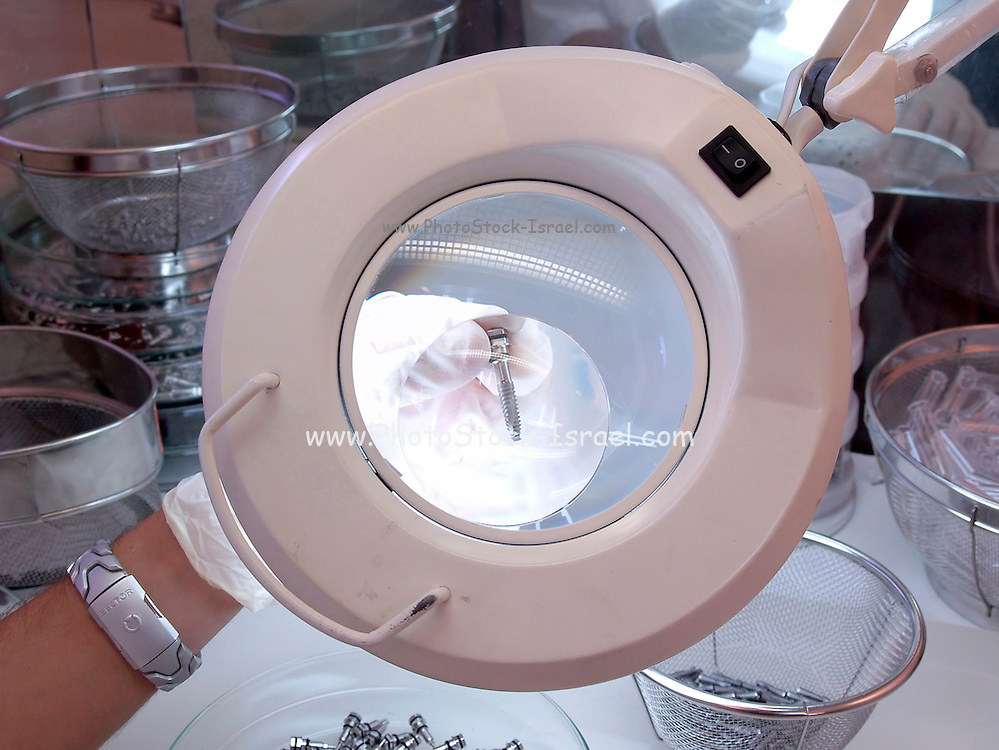 Quality control, examining a screw under a magnifying device for cracks quality problems
