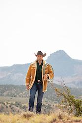 cowboy in a sheepskin coat walking on a mountain range in the desert