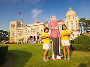 10 JANUARY 2015 - BANGKOK, THAILAND: Girls pose with a life sized cardboard cutout of General Prayuth Chan-ocha, the Prime Minister of Thailand during Children's Day festivities at Government House. National Children's Day falls on the second Saturday of the year. Thai government agencies sponsor child friendly events and the military usually opens army bases to children, who come to play on tanks and artillery pieces. This year Thai Prime Minister General Prayuth Chan-ocha, hosted several events at Government House, the Prime Minister's office.    PHOTO BY JACK KURTZ