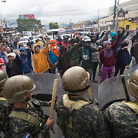 A row of soldiers confront protestors in clouds of smoke from burning tyres on barricades. The protestors sang the national anthem of Honduras during the protest was against electoral fraud by the Nationalist Party.