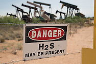 Apache Energy site with a collection of drilling derricks near the entrance in the Permian Basin in west Texas.