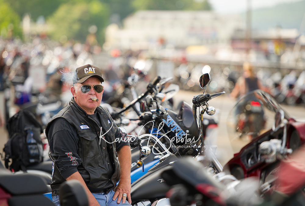 Marty Poulin of Derry enjoys a cigar as he watches motorcyclists parade down Lakeside Avenue Tuesday evening.  (Karen Bobotas/for the Laconia Daily Sun)