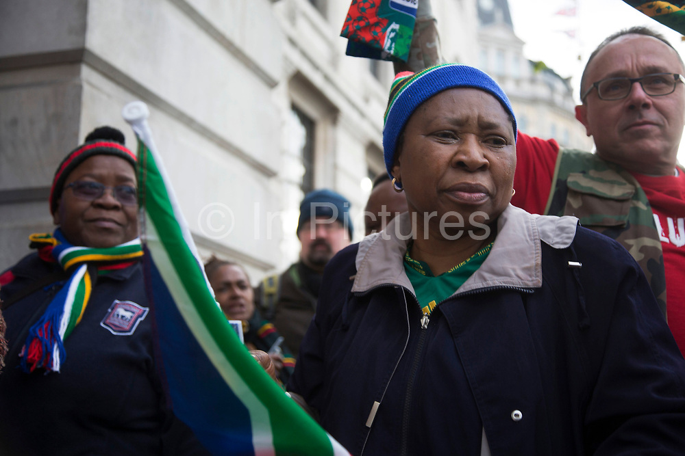 London, UK 6th December 2013: People gather with flags near to the South African Embassy to pay tribute to former South African leader and anti-apartheid ANC campaigner Nelson Mandela, who died aged 95 on 5th December 2013.