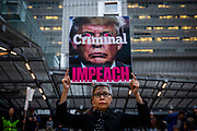 """SAN FRANCISCO, CA - DECEMBER 17: Connie Jeung-Mills of San Francisco, California holds a sign during demonstrations in part of a national impeachment rally, at the San Francisco Federal Building in San Francisco, California on December 17, 2019. Protesters around the nation participated in """"Nobody is Above the Law"""" rallies on the eve of a historic Trump impeachment vote in the United States House of Representatives. (Photo by Philip Pacheco/AFP)"""