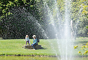 © Licensed to London News Pictures. 13/05/2015. Cliveden, UK. People enjoy the water garden. Visitors to the National Trust property Cliveden House enjoy the warm and sunny weather today 13th May 2015. Photo credit : Stephen Simpson/LNP