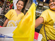 04 DECEMBER 2012 - BANGKOK, THAILAND:  A girl dressed in yellow sells Thai flags to people in front of Siriraj Hospital in Bangkok. Yellow is the official color of the Thai King, who celebrates his 85th birthday Wednesday, Dec. 5. The King lives in Siriraj. He is expected to make a rare public appearance and address the nation from Mukkhadej balcony of the Ananta Samakhom Throne Hall in the Royal Plaza. The last time he did so was in 2006. His birthday is a public holiday in Thailand and hundreds of thousands of people are expected to jam the streets around the Royal Plaza and Grand Palace to participate in the festivities.   PHOTO BY JACK KURTZ