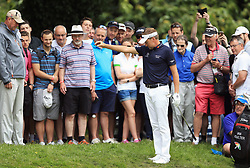 England's Ian Poulter drops his ball after it lands on a spectators bag on the third hole during day three of the 2017 BMW PGA Championship at Wentworth Golf Club, Surrey.