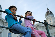 Two children (9 years old, 5 years old) wearing French berets, sitting on railing with Admiral Casino building out-of-focus in background. Opatija, Croatia