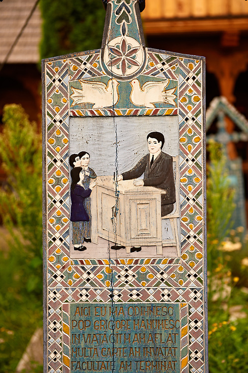 Tombstone of a school master,  The  Merry Cemetery ( Cimitirul Vesel ),  Săpânţa, Maramares, Northern Transylvania, Romania.  The naive folk art style of the tombstones created by woodcarver  Stan Ioan Pătraş (1909 - 1977) who created in his lifetime over 700 colourfully painted wooden tombstones with small relief portrait carvings of the deceased or with scenes depicting them at work or play or surprisingly showing the violent accident that killed them. Each tombstone has an inscription about the person, sometimes a light hearted  limerick in Romanian. .<br /> <br /> Visit our ROMANIA HISTORIC PLACXES PHOTO COLLECTIONS for more photos to download or buy as wall art prints https://funkystock.photoshelter.com/gallery-collection/Pictures-Images-of-Romania-Photos-of-Romanian-Historic-Landmark-Sites/C00001TITiQwAdS8
