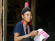 Portrait of a Ko Pala ethnic minority woman sewing outside her home in Ban Lao Li village, Phongsaly Province, Lao PDR.  She is wearing the Pala traditional headdress typical of the married woman of the Pala ethnic minority and plastic bead. One of the most ethnically diverse countries in Southeast Asia, Laos has 49 officially recognised ethnic groups although there are many more self-identified and sub groups. These groups are distinguished by their own customs, beliefs and rituals. Details down to the embroidery on a shirt, the colour of the trim and the type of skirt all help signify the wearer's ethnic and clan affiliations.