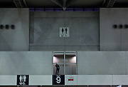 A man talks on a cellphone in an exhibition hall in Tokyo below a sign pointing the way to the toilets. Tokyo, Japan. Saturday March 23rd 2013