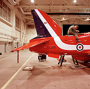 Engineer airframe specialist Junior Technician Barry Pritchard of the elite 'Red Arrows', Britain's prestigious Royal Air Force aerobatic team, forms part of the team's highly-skilled group of support ground crew who outnumber the pilots 8:1. Here J/Tech Pritchard straddles the fuselage of  the Hawk jet aircraft performing a Ram Air Turbine (RAT) jack change in the squadron hangar. Eleven trades are imported from some sixty that the RAF employs and teaches. The team's aircraft are in some cases 25 years old and their airframes require constant attention, with frequent overhauls needed. In these shelters were housed the Lancaster bombers 617 Dambusters squadron who attacked the damns of the German Ruhr valley on 16th May 1943 using the Bouncing Bomb. The Red Arrows nearby offices as their administrative nerve-centre for the 90-plus displays they perform a year. .