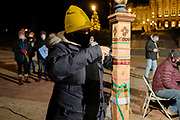 21 DECEMBER 2020 - DES MOINES, IOWA: A person ties a ribbon to a memorial pole in honor of a homeless person who died in Iowa this year. More than 100 people gathered on the steps of the State Capitol in Des Moines to honor the homeless who died in Iowa in 2020. The ceremony is held every year on December 21, the longest night of the year. Twenty-five homeless people have died in Iowa so far in 2020.     PHOTO BY JACK KURTZ