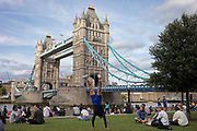 Tourist does a hand stand at Tower Bridge in London, England, United Kingdom. Scenes of both tourists and local office workers enjoying hanging out on the grass at the London Bridge City Park near to Tower Bridge. This area is an icon for tourism, bringing thousands of people in each day.