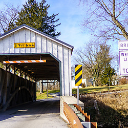 Ephrata, PA / USA – February 3, 2020: Keller's Mill Bridge is a white 74 feet covered bridge that spans the Cocalico Creek in Lancaster County. It is the only white covered bridge in the county.