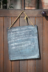Blackboard with list of jobs to do hung up on greenhouse door