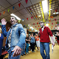 Nederland, Amsterdam , 11 juni 2013.<br /> Repetitie van de volksopera Tuindorp Oostzaan in Amsterdam Noord.<br /> De Volksopera Tuindorp Oostzaan bestaat uit beroemde aria's, duetten en koorzangen (van Puccini, Verdi, Bizet, Mozart etc.) Vertaald naar het Nederlands, niet letterlijk, maar naar een eigen verhaal, een libretto, waarin ook de geschiedenis van Tuindorp belicht wordt. <br /> <br /> Gekozen is al wel om de opkomst en ondergang van de NDSM-scheepswerf de rode draad in het verhaal te laten spelen. Dramatisch biedt dit vele mogelijkheden. Een groot deel van Tuindorp ontleende zijn/haar identiteit aan de scheepswerf. De geluiden van de werf waren tot diep in het dorp te horen. Na de grote bloeifase eind jaren 50, begin 60 van de vorige eeuw, volgde een roerige periode van stakingen, overnames en werkeloosheid. Het uiteindelijke faillissement van de werf, begin jaren 80, raakte Tuindorp tot in haar kern.<br /> <br /> Het libretto zal ook weer een liefdesverhaal bevatten. Grofweg zal de Volksopera dus gaan <br /> over het leven in Tuindorp, de sores en het geluk, tegen een achtergrond van opkomst & ondergang van de NDSM-scheepswerf, van de Watersnood van 1960, van de komst van de eerste emigranten (Turken vooral), de renovaties, het vertrek van de oude Tuindorpers en de komst van de nieuwe lichting. Over liefde, dood, jaloezie, misère en wederopstanding. En na anderhalf uur zal de goede afloop zegevieren: ondanks de tegenstellingen gaat Tuindorp Oostzaan eensgezind, hand in hand en in vrede de toekomst tegemoet. <br /> <br /> <br /> Foto:Jean-Pierre Jans