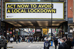© Licensed to London News Pictures. 25/10/2020. Manchester, UK. Shoppers walk under a large local lockdown sign on Market Street, Manchester. Shoppers in Manchester aren't deterred by new tier 3 restriction or potential tier 4 restrictions, which could see retail and restaurants closed. Photo credit: Kerry Elsworth/LNP