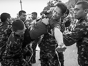 """07 MARCH 2015 - NAKHON CHAI SI, NAKHON PATHOM, THAILAND: Soldiers bring a man out of a trance after he charged the stage at the Wat Bang Phra tattoo festival. Wat Bang Phra is the best known """"Sak Yant"""" tattoo temple in Thailand. It's located in Nakhon Pathom province, about 40 miles from Bangkok. The tattoos are given with hollow stainless steel needles and are thought to possess magical powers of protection. The tattoos, which are given by Buddhist monks, are popular with soldiers, policeman and gangsters, people who generally live in harm's way. The tattoo must be activated to remain powerful and the annual Wai Khru Ceremony (tattoo festival) at the temple draws thousands of devotees who come to the temple to activate or renew the tattoos. People go into trance like states and then assume the personality of their tattoo, so people with tiger tattoos assume the personality of a tiger, people with monkey tattoos take on the personality of a monkey and so on. In recent years the tattoo festival has become popular with tourists who make the trip to Nakorn Pathom province to see a side of """"exotic"""" Thailand.   PHOTO BY JACK KURTZ"""