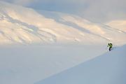 Nate Stevens skis down Hallwylfjellet, Svalbard at sunset.
