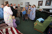 "Aug 10, 2008 -- COLORADO CITY: Members of the Jessop family have a prayer service in the living room of their home in Colorado City, AZ. The Jessops are polygamists and members of the FLDS. Colorado City and neighboring town of Hildale, UT, are home to the Fundamentalist Church of Jesus Christ of Latter Day Saints (FLDS) which split from the mainstream Church of Jesus Christ of Latter Day Saints (Mormons) after the Mormons banned plural marriage (polygamy) in 1890 so that Utah could gain statehood into the United States. The FLDS Prophet (leader), Warren Jeffs, has been convicted in Utah of ""rape as an accomplice"" for arranging the marriage of teenage girl to her cousin and is currently on trial for similar, those less serious, charges in Arizona. After Texas child protection authorities raided the Yearning for Zion Ranch, (the FLDS compound in Eldorado, TX) many members of the FLDS community in Colorado City/Hildale fear either Arizona or Utah authorities could raid their homes in the same way. Older members of the community still remember the Short Creek Raid of 1953 when Arizona authorities using National Guard troops, raided the community, arresting the men and placing women and children in ""protective"" custody. After two years in foster care, the women and children returned to their homes. After the raid, the FLDS Church eliminated any connection to the ""Short Creek raid"" by renaming their town Colorado City in Arizona and Hildale in Utah.     Photo by Jack Kurtz / ZUMA Press"