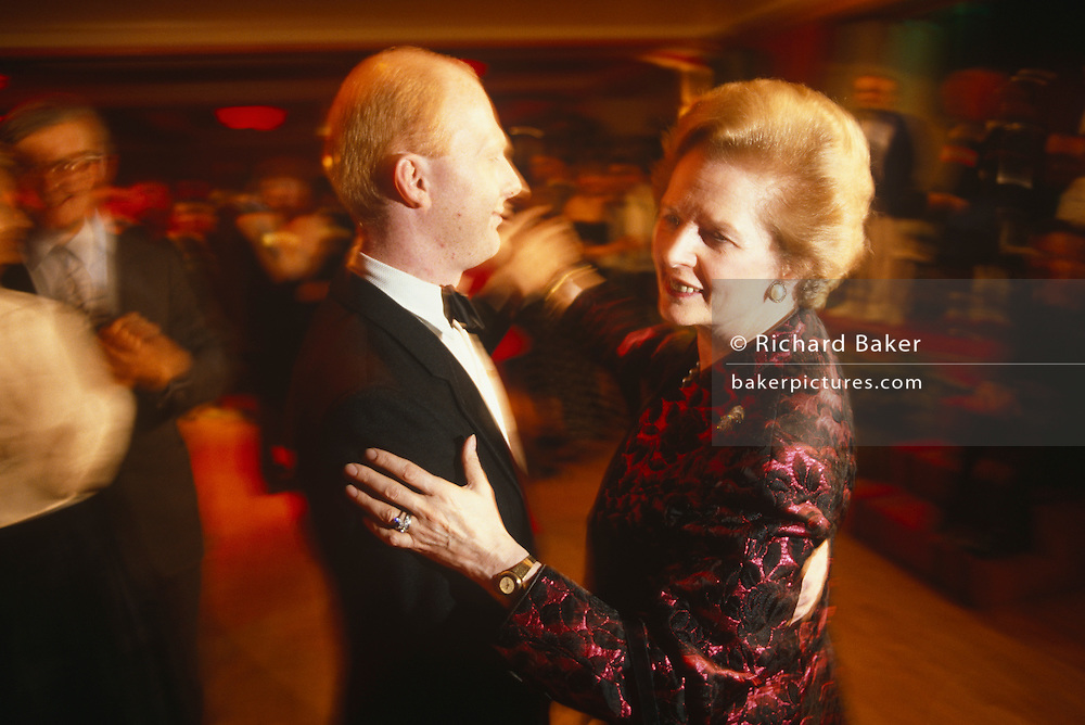 Prime Minister Margaret Thatcher is seen dancing with a Tory Party official during the 1990 Conservative Party conference in Blackpool. Thatcher is wearing a favourite black and red ball gown and is the centre of attention for delegates and media whose TV lights have lit the dancing couple from the right-hand side. Her partner is young and has acne and is wearing a formal dinner jacket and bow tie. The image is warm from the ambient light and there is a slight blur of movement as they sweep past the viewer.