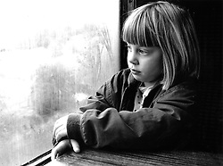 Young girl sitting at table staring out of window,