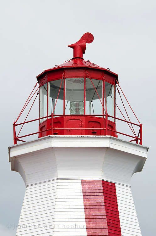 The lantern of the red-and-white painted East Quoddy Lighthouse gleams in a ray of sun against a stormy gray sky.