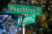 "A confusing pair of street signs showing two of the 71 Peachtree street and road names known in Atlanta. It is often joked that half of the streets in Atlanta are named Peachtree, and the other half have five names to make up for it. While ""Peachtree"" alone always refers to this street, there are 71 streets in Atlanta with a variant of ""Peachtree"" in their name. The first Peachtree was a Creek Indian village on the Chattahoochee River called Standing Peachtree. An army outpost built nearby took the name Fort Peachtree. From this has come a forest of Peachtrees. In Margaret Mitchell's epic Civil War romance Gone With the Wind, Scarlett O'Hara lives on various points of Peachtree Street along the novel."