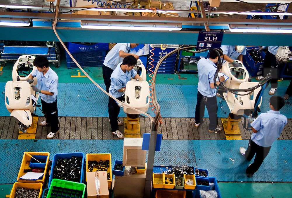 Workers assemble Vespas on the assembly line at the Piaggio Factory outside Hanoi, Vietnam
