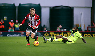 Brentford defender Jake Bidwell leaving Hudderfield Town striker Ishmael Miller on the floor during the Sky Bet Championship match between Brentford and Huddersfield Town at Griffin Park, London, England on 19 December 2015. Photo by Matthew Redman.