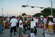 Protesters block an intersection at Craig Ranch North in response to an incident with teens and police officers at a community pool in McKinney, Texas on June 8, 2015.  (Cooper Neill for The New York Times)
