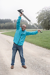 Senior man stretching before Nordic walk with hiking poles, Bavaria, Germany