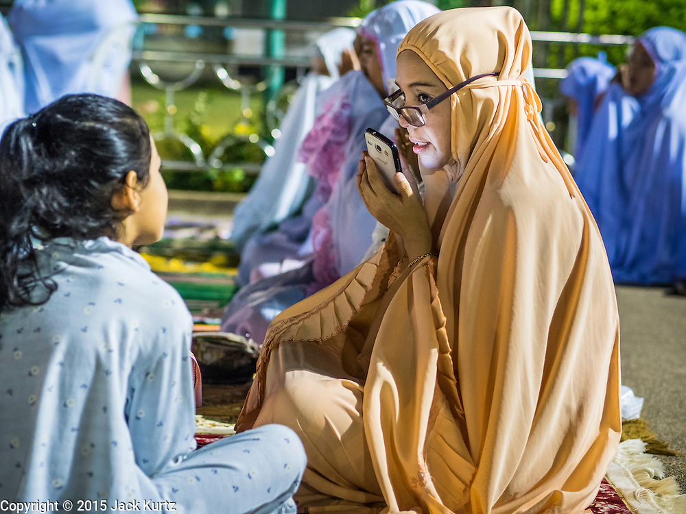 18 JUNE 2015 - PATTANI, PATTANI, THAILAND:  A woman uses her smart phone after Ramadan services at Pattani Central Mosque. Thousands of people come to Pattani Central Mosque in Pattani, Thailand, to mark the first night of Ramadan. Ramadan is the ninth month of the Islamic calendar, and is observed by Muslims worldwide as a month of fasting to commemorate the first revelation of the Quran to Muhammad according to Islamic belief. This annual observance is regarded as one of the Five Pillars of Islam. Islam is the second largest religion in Thailand. Pattani, along with Narathiwat and Yala provinces, all on the Malaysian border, have a Muslim majority.      PHOTO BY JACK KURTZ