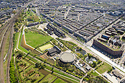 Nederland, Noord-Holland, Amsterdam, 09-04-2014;<br /> Cultuurpark Westergasfabriek en Westerpark op het voormalige  Westergasterrein langs Haarlemmerweg, andere kant van het kanaal woonwijk de multiculturele Staatsliedenbuurt met het voormalig waterleidingterrein en de watertoren in Waterwijk. <br /> Spoor met treinen boven in beeld. Spaarndammerbuurt.<br /> Buildings of Culture park Westergasfabriek and the Westerpark on the former Westergasterrein (gasworks) along the railroad from Amsterdam Central station. View on the North of Amsterdam.<br /> luchtfoto (toeslag op standard tarieven);<br /> aerial photo (additional fee required);<br /> copyright foto/photo Siebe Swart
