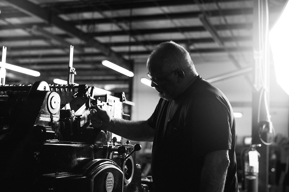 BIRMINGHAM, AL –SEPTEMBER, 2017: Technicians and laborers work on the floor of a commercial offset printing plant.