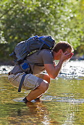 male hiker cooling off in a river