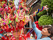"""23 JUNE 2015 - MAHACHAI, SAMUT SAKHON, THAILAND:  A toy vendor at the City Pillar Shrine procession in Mahachai. The Chaopho Lak Mueang Procession (City Pillar Shrine Procession) is a religious festival that takes place in June in front of city hall in Mahachai. The """"Chaopho Lak Mueang"""" is  placed on a fishing boat and taken across the Tha Chin River from Talat Maha Chai to Tha Chalom in the area of Wat Suwannaram and then paraded through the community before returning to the temple in Mahachai.  PHOTO BY JACK KURTZ"""