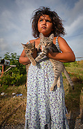 Angel with her cats of the Biloxi-Chimacha-Choctaw tribe on Isle de Jean Charles holds two kittens.