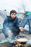 A man from Syria cooks food for himself and his friends.