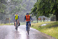 Licensed to London News Pictures. 12/07/2021. London, UK. Cyclists get caught in torrential rain in Richmond Park, southwest London this afternoon with roads and pavements becoming quickly flooded as the Met Office issue yellow weather warnings for heavy rain and thunderstorms which may cause disruption to travel and flooding. However, sunshine and warm weather is predicted for the rest of the week with highs of 26c for the weekend.. Photo credit: Alex Lentati/LNP