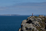 Man taking a selfie on his smartphone at Pointe du Van on 23rd September 2021 in Plogoff, Brittany, France. The Pointe du Van is a promontory that extends into the Atlantic from western Brittany. The local Breton name is Beg ar Vann. It is located in the commune of Plogoff, Finistère. Brittany is a peninsula, historical county, and cultural area in the west of France, covering the western part of what was known as Armorica during the period of Roman occupation. It became an independent kingdom and then a duchy before being united with the Kingdom of France in 1532 as a province governed as a separate nation under the crown.