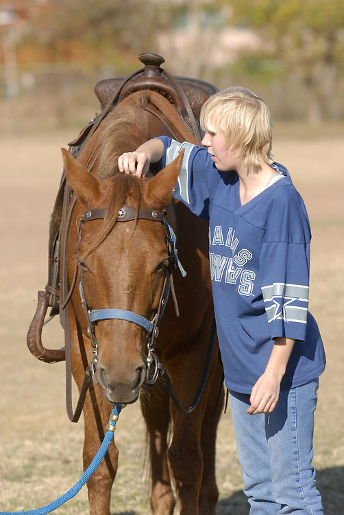 Austin, Texas December 13, 2006: A ninth-grade student who attends Texas School for the Blind and Visually Impaired (TSVBI) experiences horse-riding for the first time during an outing at the school in central Austin.  Area ranchers bring horses to campus once a year to offer new experiences and help build self-confidence for legally blind students.          ©Bob Daemmrich/