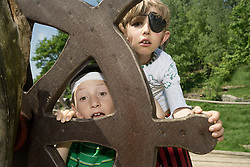 Two boys peeking from rudder of a pirate ship in adventure playground, Bavaria, Germany