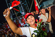01 MARCH 2013 - BANGKOK, THAILAND: .Thai women cheer for NATTAWUT SAI-KUA (not in picture) during the last election rally Pongsapat Pongchareon who is running for governor of Bangkok Nattuwat is a popular Red Shirt leader and member of Thai Parliament from the Pheu Thai party. The election is Sunday, March 3 and no campaigning is allowed 24 hours before election day. Police General Pongsapat Pongcharoen (retired), a former deputy national police chief who also served as secretary-general of the Narcotics Control Board is the Pheu Thai Party candidate in the upcoming Bangkok governor's election. He resigned from the police force to run for Governor. Former Prime Minister Thaksin Shinawatra reportedly personally recruited Pongsapat. Most of Thailand's reputable polls have reported that Pongsapat is leading in the race and likely to defeat Sukhumbhand Paribatra, the Thai Democrats' candidate and incumbent. The loss of Bangkok would be a serious blow to the Democrats, whose national base has been the Bangkok area.    PHOTO BY JACK KURTZ